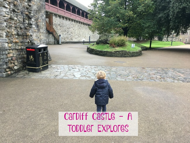 Cardiff-Castle-A-Toddler-Explores-text-on-image-of-toddler-in-cardiff-castle-grounds