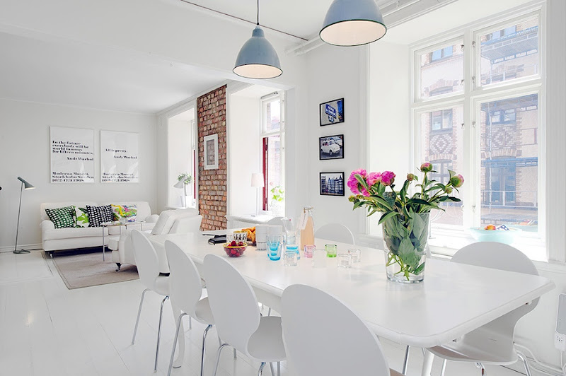 View of the white living room and dining room with blue pendant lights, large windows, white table and chairs