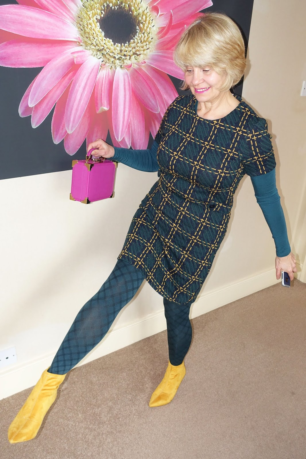Stylish diamond patterned tights in spruce pull this outfit of a spruce top worn under a green and yellow dress and yellow ankle boots with a splash of pink.