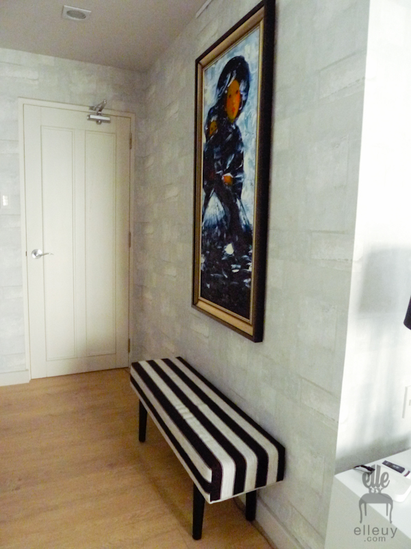 white textured wall paper with stripes bench and artwork