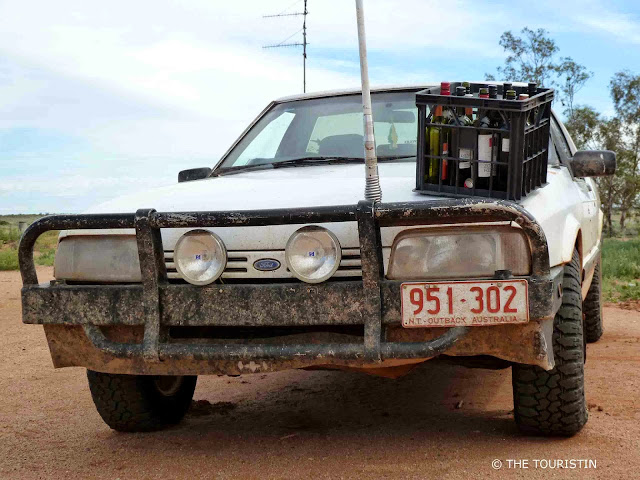 A white four-wheeled vehicle with black protection in its front and a crate of empty wine bottles on its hood, parked on a red dusty road.