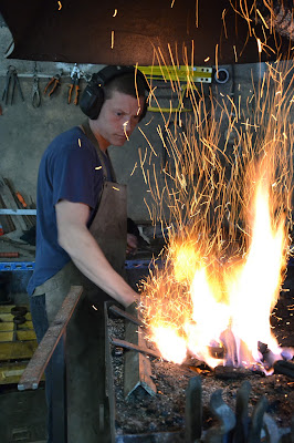 Nantz Jean-Christophe, le ferronnier, chauffe un barre de métal à la forge.