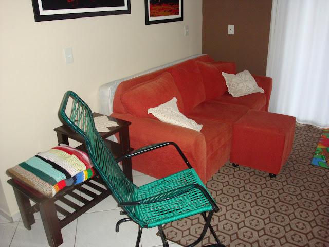 Sofás vermelhos e manta colorida para os dias frios