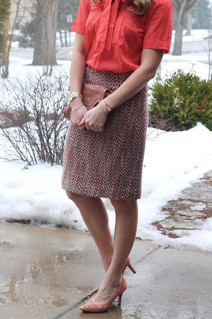 coral bow tie top, pink tweed skirt, blush heels, and blush bag