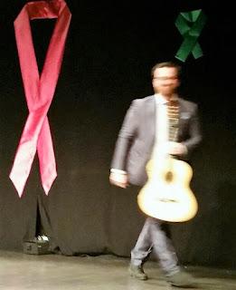 Fotografía de Félix Crujera en recital solidario contra el cáncer. Guitarra en mano junto a un lazo rojo