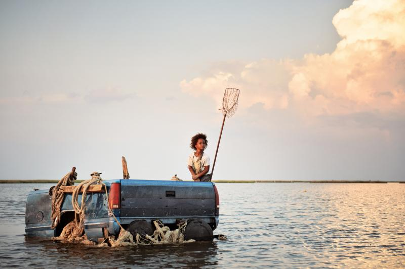 Hushpuppy adrift on open water, horizon far away, in a repurposed truck bed