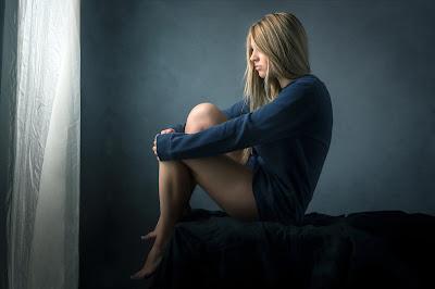 Chica rubia sentada en la cama mirando por la ventana