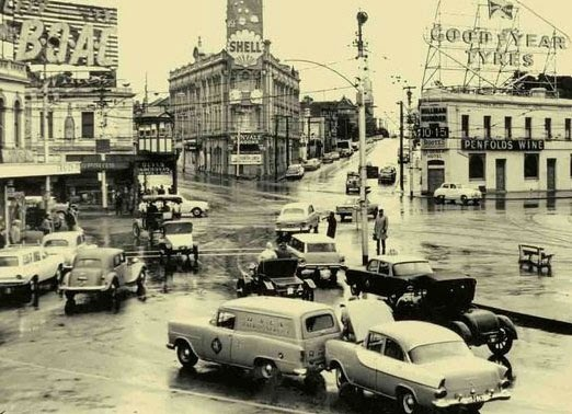 Traffic accident and traffic jostling through the roundabout at St Kilda Junction. (1962)