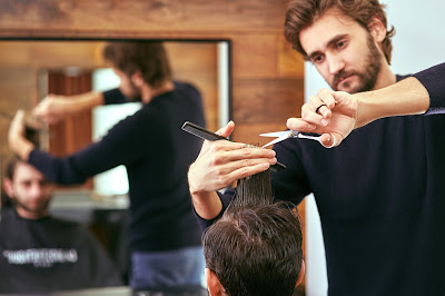 Pic of barber cutting man's hair with sharp scissors and comb reflected in mirror
