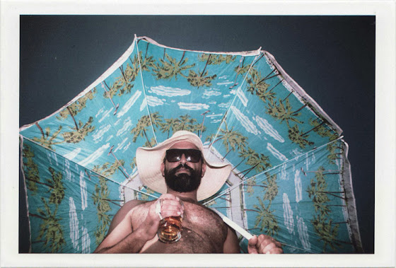 dirty photos - on the island of - photo of man holding a beer and a huge umbrella at the beach