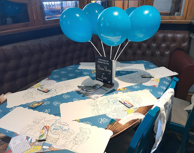 table set up for pizza party with balloons, colouring sheets and aprons