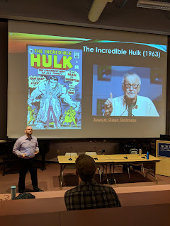 Lance is standing at the front of the room with a large image of the Incredible Hulk and Stan Lee behind him on the screen.