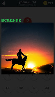 В свете солнечных лучей на закате виден силуэт всадника в фуражке
