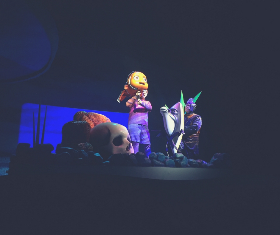 A puppet of Nemo, from Finding Nemo, a person dressed in a purple suit controls the puppet from underneath.