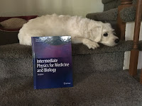 Suki Roth, in front of a copy of Intermediate Physics for Medicine and Biology.