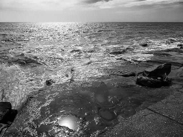 El rompe contra las piedras y la luz refleja sobre el mar.