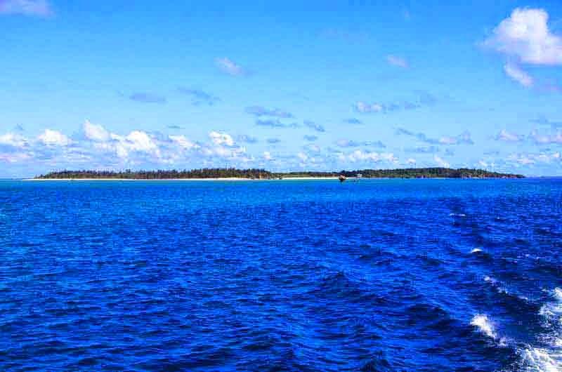 island in blue seas under blue skies