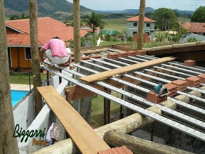 Detalhe da armação da laje do piso em cima das vigas de madeira de eucalipto tratado com os pilares de madeira com a alvenaria de bloco de cimento em construção de sala de estar com a suíte superior em construção rústica no sul de Minas Gerais.
