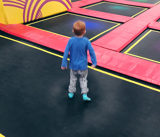 Back view of a little boy bouncing on a large trampoline
