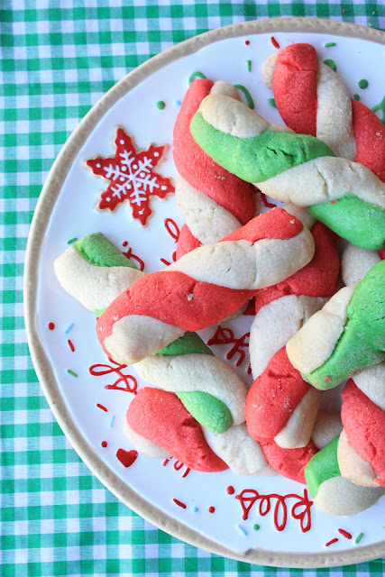 twisted red and green peppermint stick cookies stacked on a holiday cookie tray