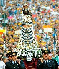 Una processione cattolica romana dietro una statuta.