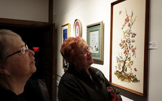 two women looking at an embroidered picture called tree of life; it features Canada's provincial flowers