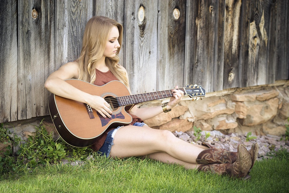 Beautiful girl sitting playing acoustic guitar