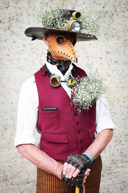 Steampunk Plague Doctor cosplay. Man wearing leather plague doctor mask, hat with babies breath flowers, vest, ascot, cane, and striped pants.