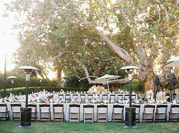 Outdoor wedding reception in Malibu beneath string cafe lights | Photo by Matoli Keely Photography