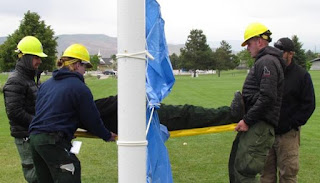 "On the right, Boise BLMer Carl Bernardi passes his teammate Damian Martinez through the ""electric fence"" to two USFS employees – without sizzling him on the tarp."