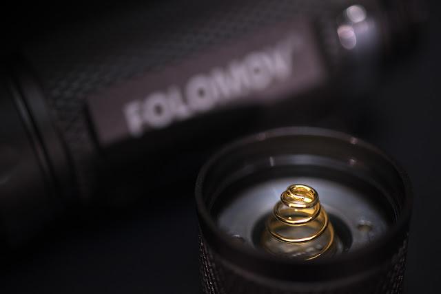 Tylna nakrętka w latarce Folomov 18650s z widoczną sprężynką dociskającą