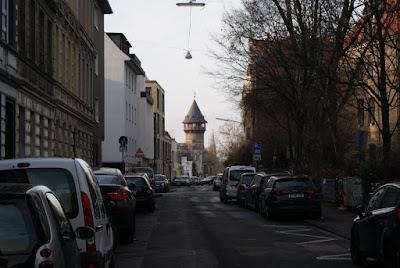 Eine Straße, an deren Seite viele Autos parken. In der Bildmitte aber im Hintergrund ein hoher Turm mit hölzernem Spitzdach.
