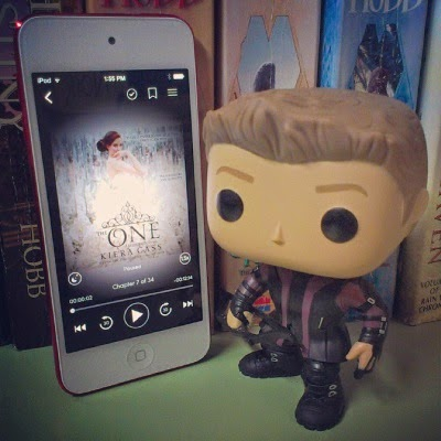 Tiny Hawkguy, a four-inch bobblehead wearing a black-and-purple superhero outfit and carrying a tiny bow, stands next to an upright white iPod with red edges. The iPod's screen displays the cover of The One, featuring a red-haired white girl in a white ballgown.