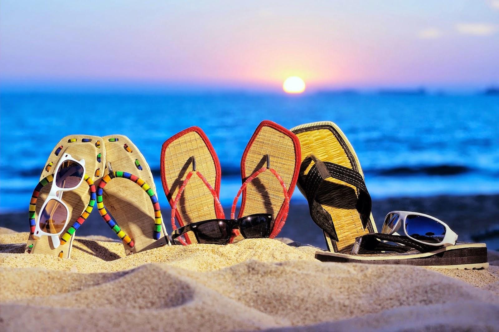 Slippers en zonnebrillen op het strand in de zomer