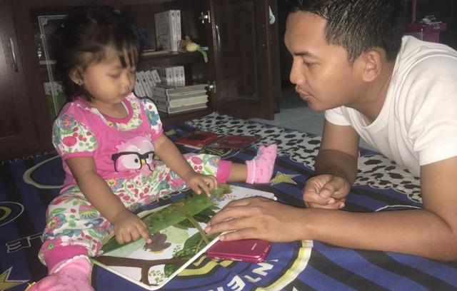 Izza membaca cerita dengan ayah di malam hari