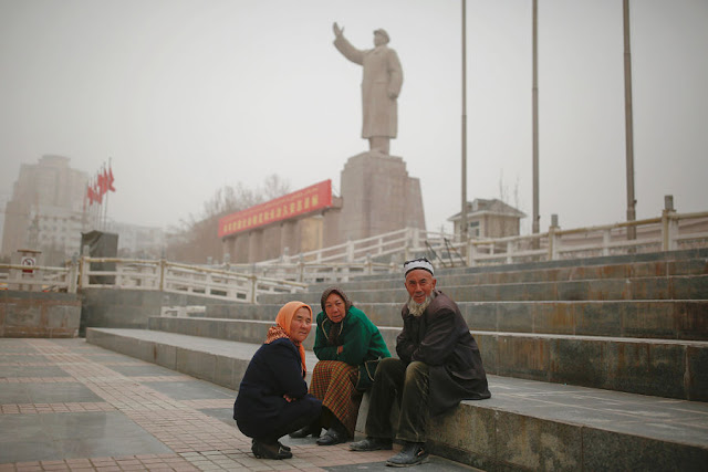 Image Attribute: Ethnic Uighurs sit near a statue of China's late Chairman Mao Zedong in Kashgar, Xinjiang Uighur Autonomous Region, China, March 23, 2017. REUTERS/Thomas Peter