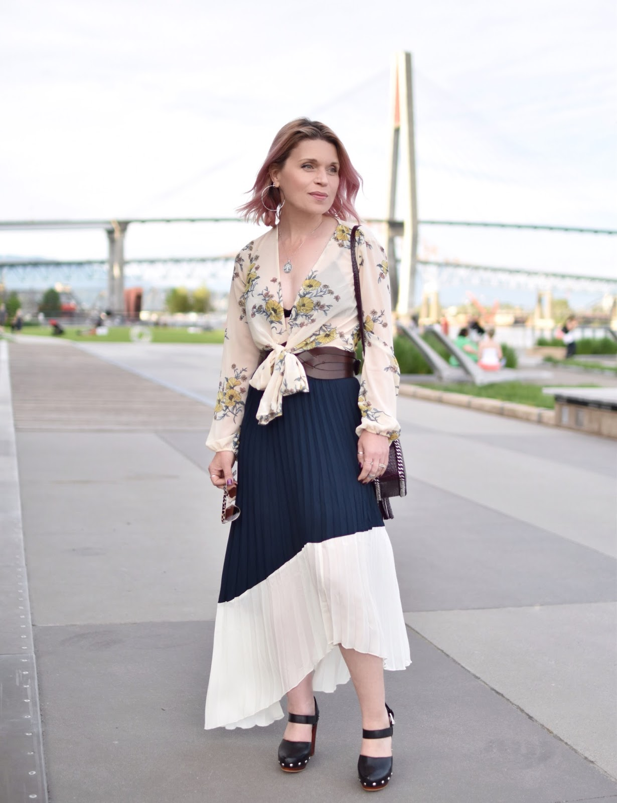 Monika Faulkner outfit inspiration - styling a pleated maxi skirt with a floral blouse, corset belt, and platform mary-jane shoes