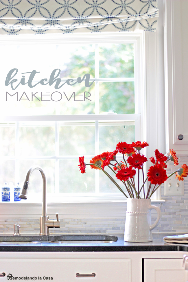 white and grey kitchen with roman shade and red-orange gerbera daisies