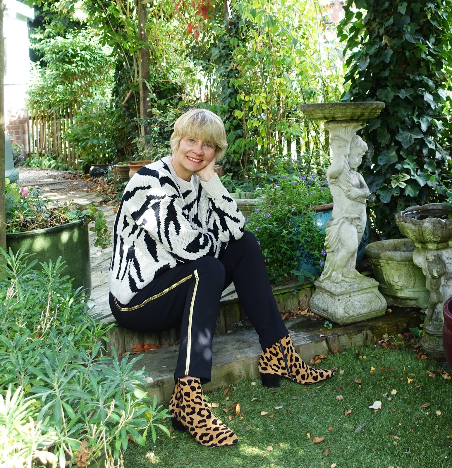 Over 45s blogger Gail Hanlon mixing animal prints with a zebra jumper from Asos and leopard print ankle boots from Office, worn with black trousers with a gold side stripe