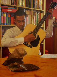 A Missionary from The Church of Jesus Christ of Latter Day Saints playing the guitar in a members home
