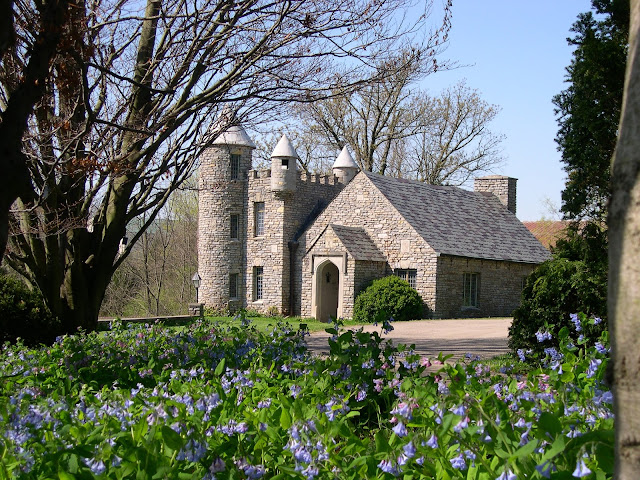 the stone house at yew dell gardens with turrets and the gardens in front with pretty blue flowers in the field