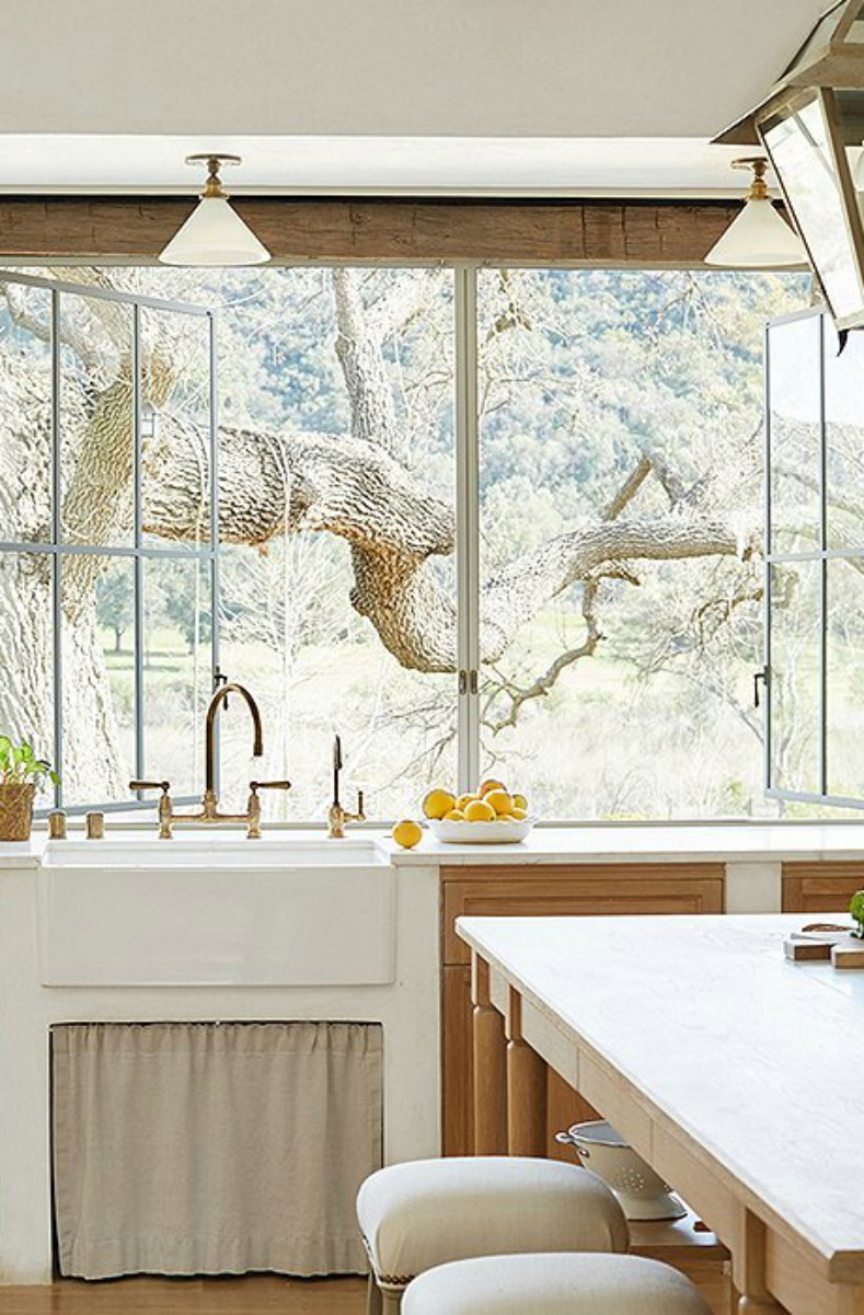 Magnificent tree at kitchen window of #farmhousekitchen with #farmsink, white oak cabinetry, and plaster walls