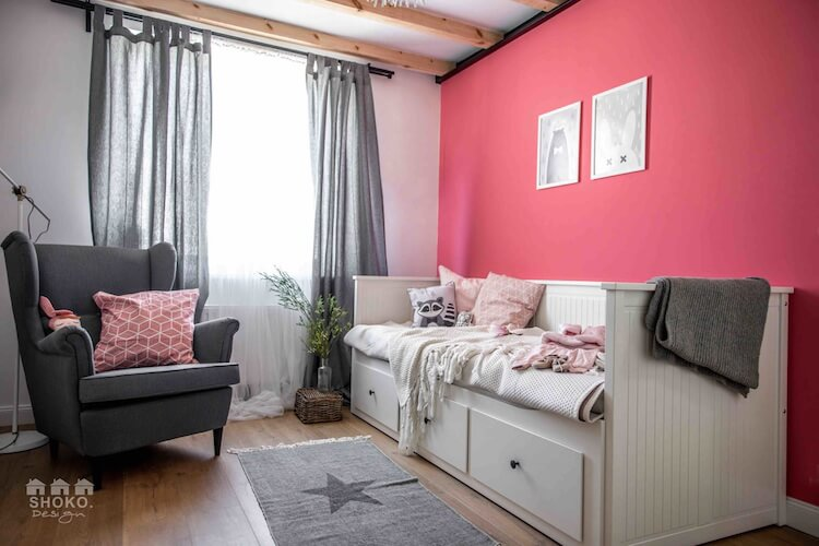 dormitorio con pared rosa, vigas de madera y detalles en gris