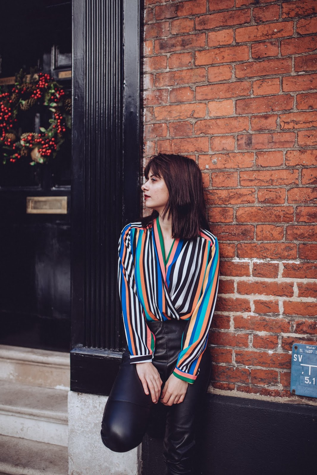 Me next to a red brick wall wearing a rainbow stripped top and faux leather trousers