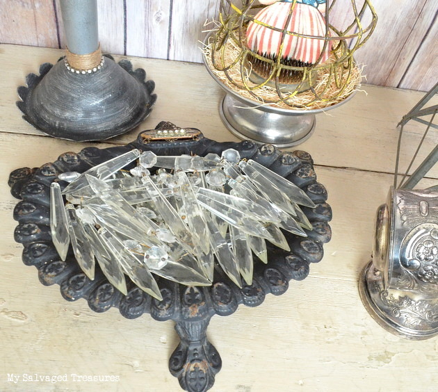 chandelier crystals displayed in a vintage cast iron fireplace tool set base.