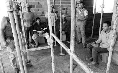 Pedreiros e serventes se confraternizam após a concretagem de uma laje. A execução de um projeto arquitetônico gera muitos empregos e movimenta a economia em diversos níveis.