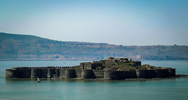 About 165 km south of Mumbai in the Raigad district of Maharashtra is Murud Janjira, one of the strongest marine forts of India and the only unconquered one along India's western coast. Famous for its beaches, the glittering sandy coastline and the villages hemmed with coconut groves, the town of Murud-Janjira attracts large crowds over weekends from Mumbai, which is merely 150 km away. Needless to say, the sea fort is the center of all activity in this small town.  Sailboats from Rajapuri jetty are the only way to approach the fort that is spread across 22 acres. The fort has 19 bastions which still stand intact and its main gate can be only be visible when one is very close to it. The fort also has a small gate that opens to the sea as an escape route. The fort's well is a marvel as it contains sweet water (despite being in the middle of the sea) and it is defended by cannons. In its heyday, the fort had palaces, mosques, fresh water tanks, markets and quarters for officers.  Janjira is derived from the Arabic word Jazeera which means island. The original structure was built in the 15th century by a Koli chief as defense against sea robbers and thieves.