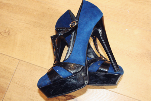 electric blue and black platform heels laying over each other on a wooden floor