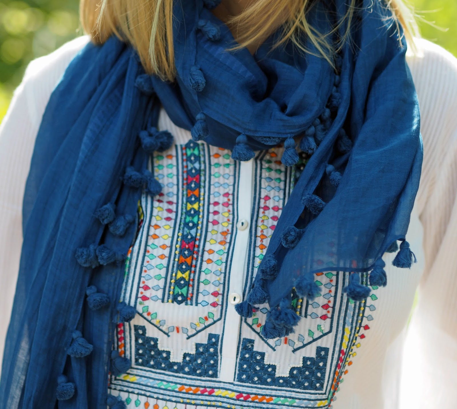 Embroidered white top with blue pompom scarf