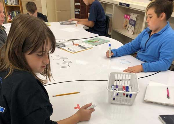 girl and boys at whiteboard tables in school library with dry erase markers drawing bridges.